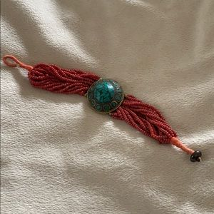 Beaded red bracelet with turquoise stone